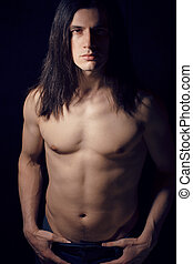 handsome young man with long hair naked torso on black...