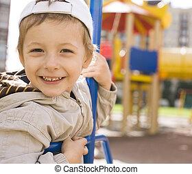 little cute boy on swing outside