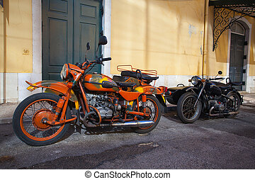 Two historic motorcycle with sidecar on a street