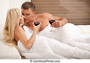 Couple drinking on the bed in bedroom
