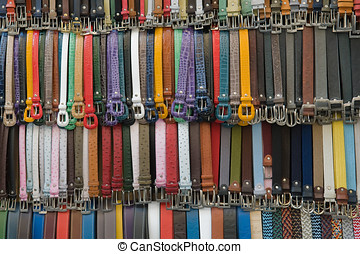 many colored leather belts on a market