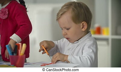 Artistic Corner - Close up of small boy cutting out figures...
