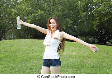 Female breaks standing and holding a bottle of water.