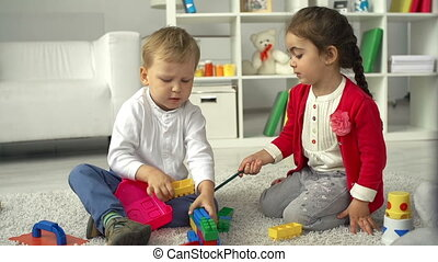 Playroom for Two - Boy and girl playing on the nursery floor...