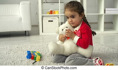 Favorite Toy - Little girl playing with teddy bear