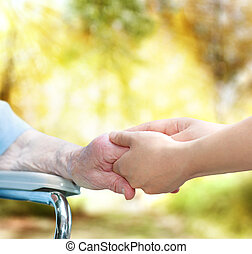 Senior lady in wheel chair holding hands with young...