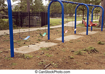 Swings at a abandoned playground around pine trees