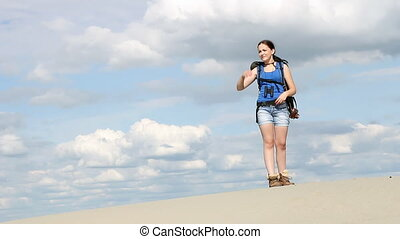 girl stands in the desert and watching with binoculars