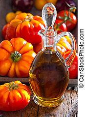 Carafe of olive oil and ripe beef tomatoes - Carafe of olive...