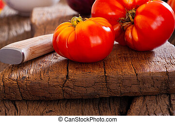 Closeup of a beef tomato and kitchen knife - Close up of a...