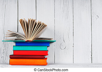 The open book on other multi-coloured books. On a wooden...