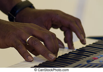 Black hands on a piano keyboard - A musicians hands playing...