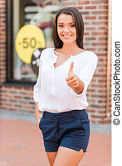 Great sale! Beautiful young woman showing her thumb up and smiling while standing against clothing store