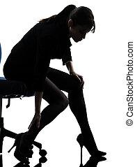 business woman massaging her leg silhouette