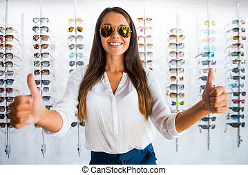 Good choice. Beautiful young woman in sunglasses showing her thumbs up and smiling while standing in optic store
