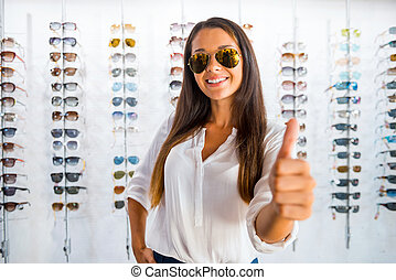 She made a right choice. Beautiful young woman in sunglasses showing her thumb up and smiling while standing in optic store
