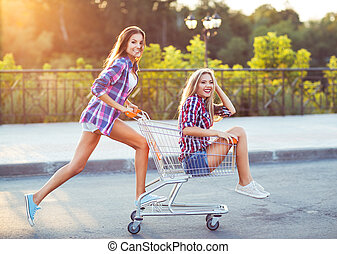 Two happy beautiful teen girls driving shopping cart...