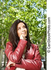 happy woman thinking - pretty brunette woman with red...
