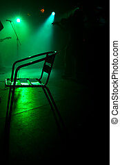 Chair on the stage in green backlight with a fiddler - Green...