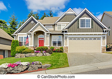 American house with beautiful landscape and vivid flowers -...
