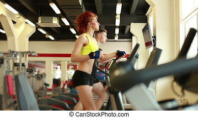 Young people exercising on treadmills in gym - View of young...