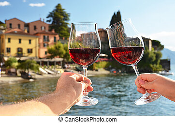 Two wineglasses in the hands. Varenna town at the lake Como,...