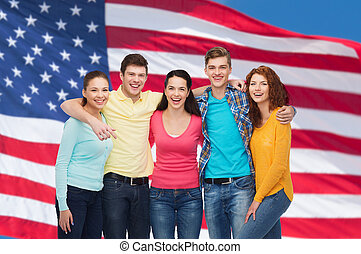 group of smiling teenagers over american flag - friendship,...