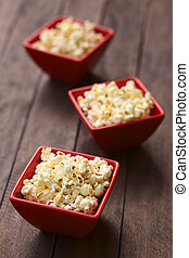 Popcorn - Three red bowls of freshly prepared salted popcorn...
