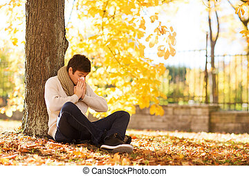smiling young man with tablet pc in autumn park - season,...
