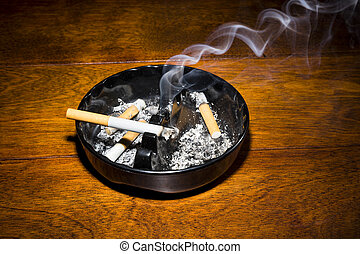 Smoking cigarette in ashtray - A burning cigar in a classic...