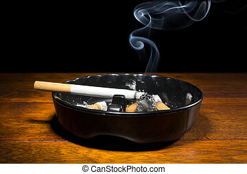 Cigarette in ashtray - A burning cigar in a classic black...