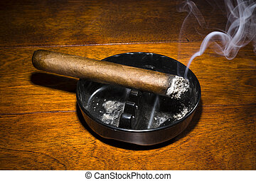 Cigar smoking in ashtray - A burning cigar in a classic...