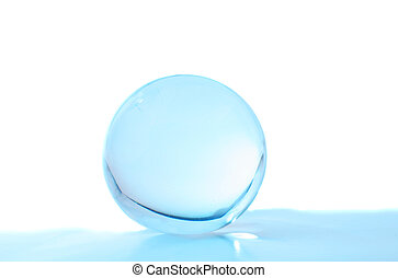 Crystal ball with turqouise light inside an foreground with...