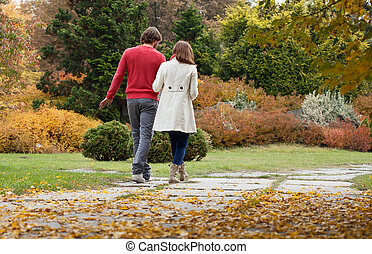 Happy couple in park during autumn walking