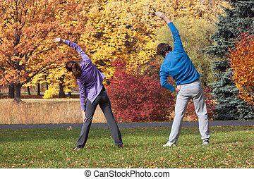 Doing stretching exercises - Couple doing stretching...