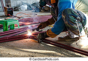 Worker welding the steel part - Worker welding the steel...