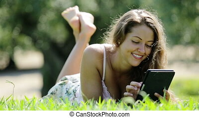 girl lying on grass - Relaxed girl lying on grass in meadow...