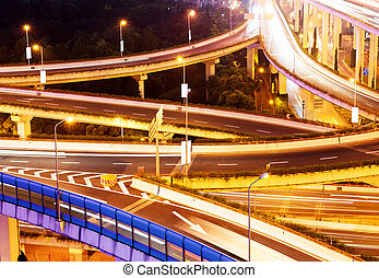 Viaduct - Freeway in night with cars light in modern city