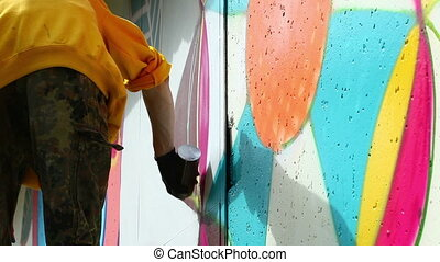 Young man drawing graffiti on wall with spray can