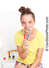 Teenager with paintbrushes