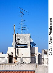 Old television aerial on house roof against blue sky