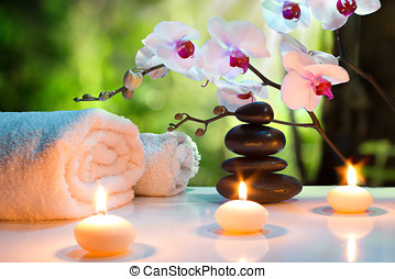 massage composition spa with candles, orchids, stones in garden
