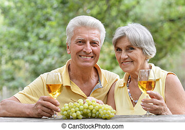 Mature couple drinking wine with bunch of grape at the table