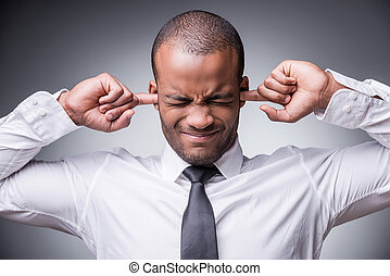 Too loud sound. Young African man in shirt and tie covering...