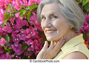 Senior woman on background of flowers - Portrait of a senior...