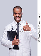 Good news. Cheerful African doctor showing his thumb up and smiling while standing against grey background