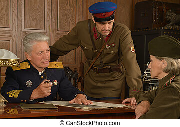 General on the table with soldiers - Military mature general...
