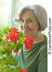 Senior woman with red flowers - Portrait of a senior woman...