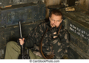 Thoughtful armed soldier sits among munitions close-up