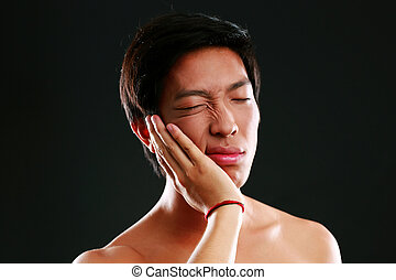 Closeup portrait of a Young Asian man with toothache
